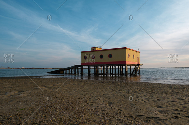 Lifeguard house located on wet sandy Fuseta Beach on background of sea and sunset sky in Algarve