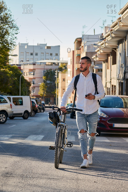 Full body of serious adult bearded male in trendy ripped jeans with backpack checking information on mobile phone while walking with bicycle on paved urban street