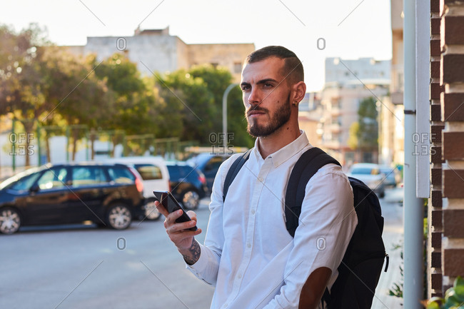 Serious adult bearded male in trendy ripped jeans with backpack checking information on mobile phone while walking with bicycle on paved urban street