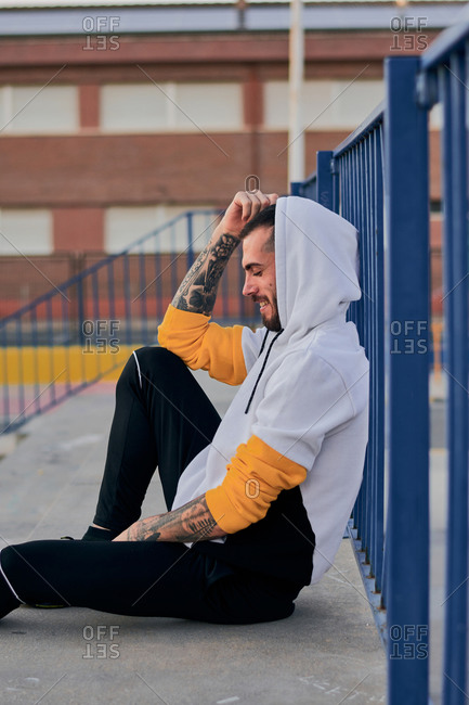 Side view full of adult bearded male with tattooed arms dressed in casual hoodie sitting on metal fence near street lamp in city