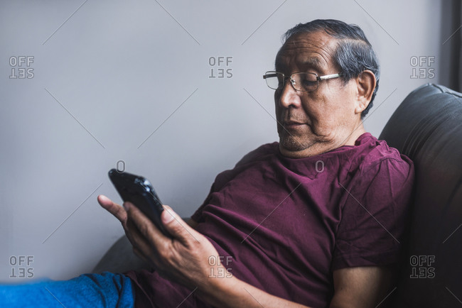 Senior ethnic male in glasses relaxing on couch in living room and reading messages on smartphone
