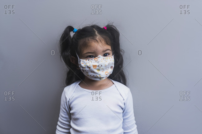 Cute ethnic little girl wearing protective mask standing on gray background and looking away during COVID 19 pandemic