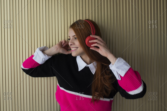 Delighted female millennial in trendy outfit standing near wall and listening to music in headphones while looking at camera and smiling
