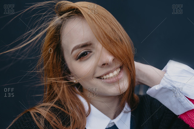 Young content redhead female with wind in hair standing in city and looking at camera