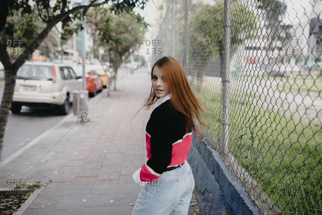 Back view of female millennial in trendy clothes walking along street and looking at camera over shoulder