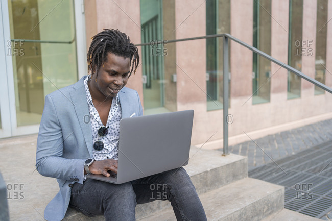 Busy African American male entrepreneur sitting on stairs of building and typing on laptop while working on remote project online in street