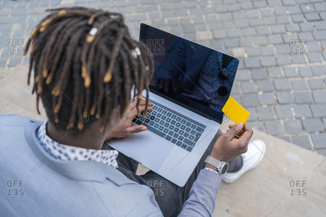 From above of unrecognizable African American male paying with plastic card while making online purchase via laptop and sitting on street