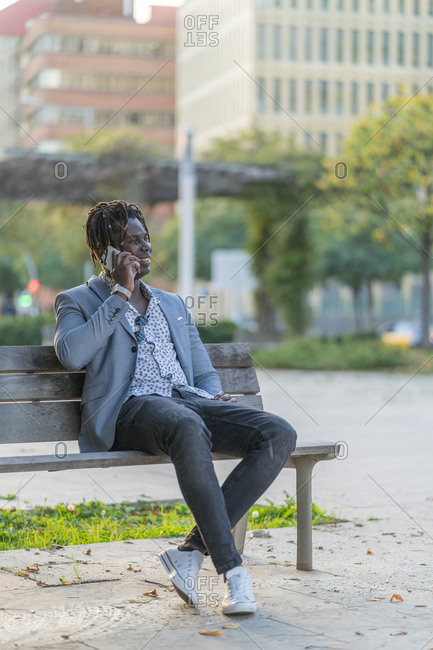 Cheerful African American male sitting on bench in city and talking smartphone while communicating on social media and relaxing at weekend