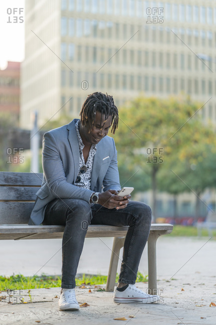 Cheerful African American male sitting on bench in city and reading messages on smartphone while communicating on social media and relaxing at weekend