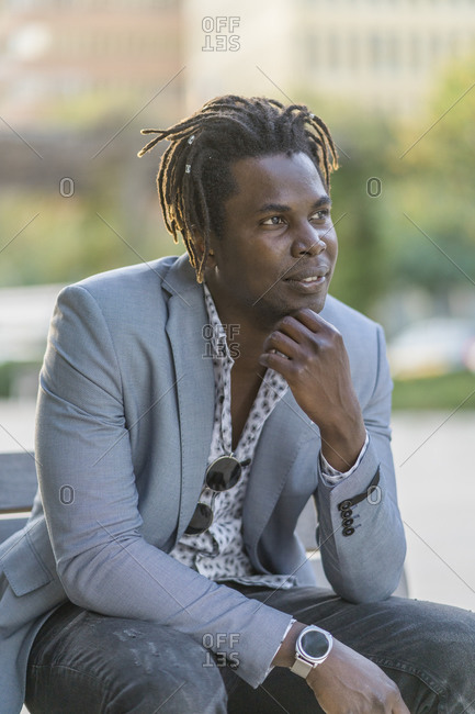 Thoughtful black male in stylish outfit and with dreadlocks sitting on bench and leaning on hand while dreaming and looking away