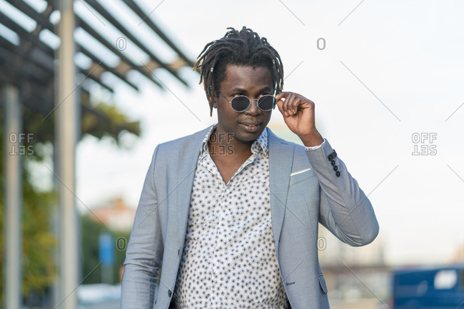 Handsome African American male with dreadlocks and in trendy round sunglasses walking along city street and looking away