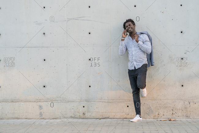Cheerful African American male leaning on urban building and speaking on smartphone while smiling and looking away