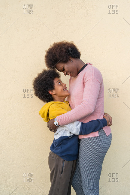 Side view of tender African American woman and boy embracing on street and looking at each other while standing in city against beige wall