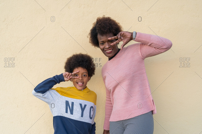 Delighted African American mother and son standing near wall in street and showing two fingers sign while looking at camera