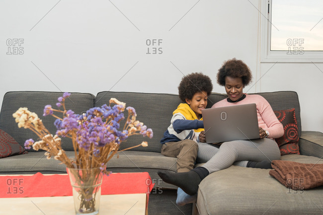 Content African American mother and son sitting on sofa with laptop and choosing movie for watching while spending time together at home