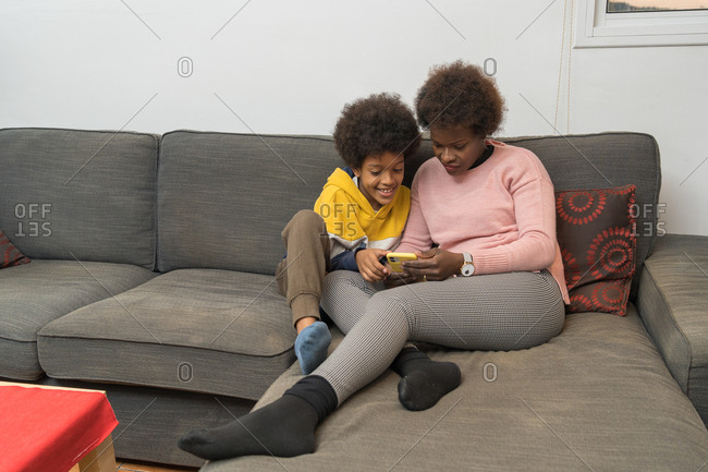 Positive African American mother and boy chilling on sofa and playing video game on smartphone while enjoying weekend and having fun at home
