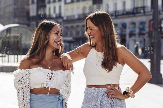 Cheerful young female friends standing happily together while having meeting on urban square in summer day looking at each other
