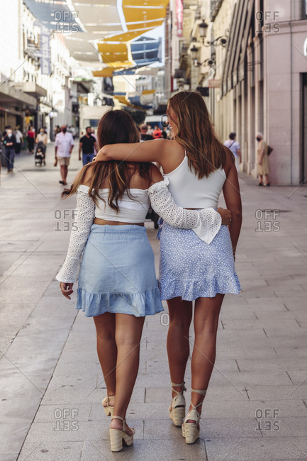 Full body back view of unrecognizable millennial girlfriends in similar summer outfits hugging and walking along urban street while spending weekend together in city