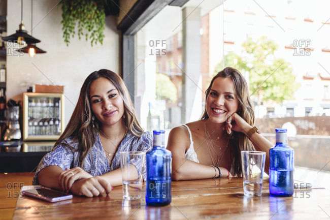 Smiling young girlfriends looking at camera while sitting at table with drinks during meeting in modern cafeteria in summer day