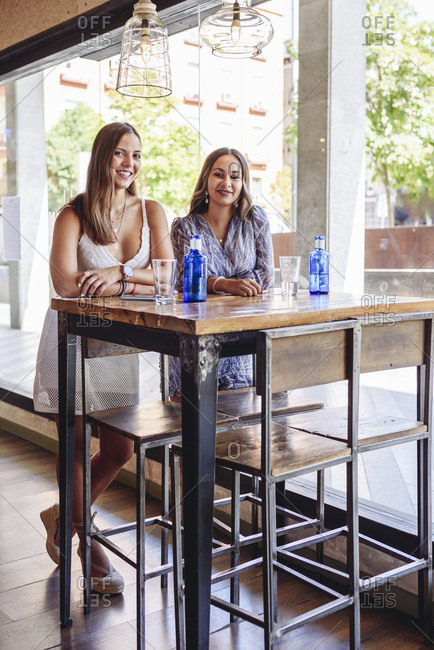 Smiling young girlfriends looking at camera while standing at table with drinks during meeting in modern cafeteria in summer day