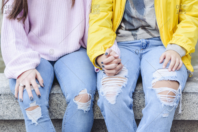 Crop unrecognizable couple of women in love holding hands while sitting on stone bench in city