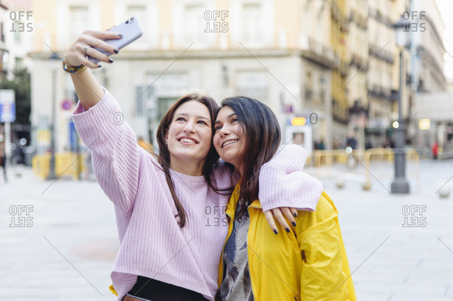Smiling lesbian females embracing in city and taking self portrait on smartphone while spending time together at weekend