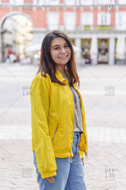 Side view of young charming female in casual bright outfit standing in street and looking at camera