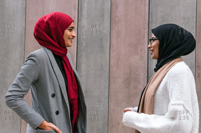 Side view of Arab female friends in traditional hijab standing together talking on the street and looking at each other