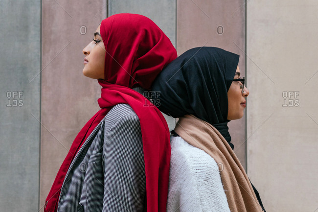 Side view of Arab female friends in traditional hijab standing back to back on street and looking away