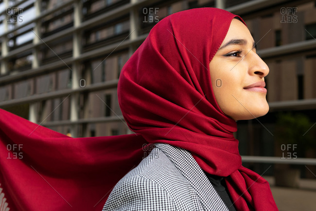Side view of young content Arab female wearing red hijab standing on street and looking away