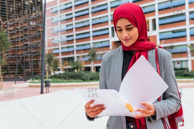 Arab female student in traditional headscarf sitting in street and reading documents for homework