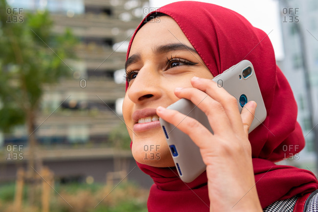 Low angle of positive ethnic female in hijab standing on street speaking on smartphone enjoying weekend