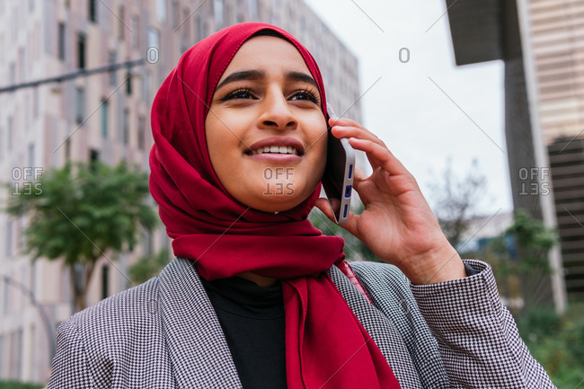 Content Arab female in red traditional headscarf standing in street and speaking on mobile phone while looking away