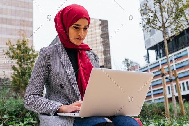 Busy Arab female entrepreneur in traditional headscarf sitting on street with laptop and working on new business project