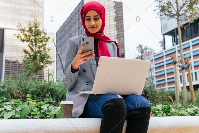 Cheerful Arab female freelancer in red hijab sitting with laptop on bench in city and browsing smartphone while working on startup project remotely
