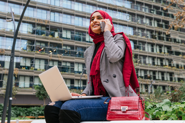 Cheerful Arab female freelancer in red hijab sitting with laptop on bench in city speaking on smartphone while working on startup project remotely