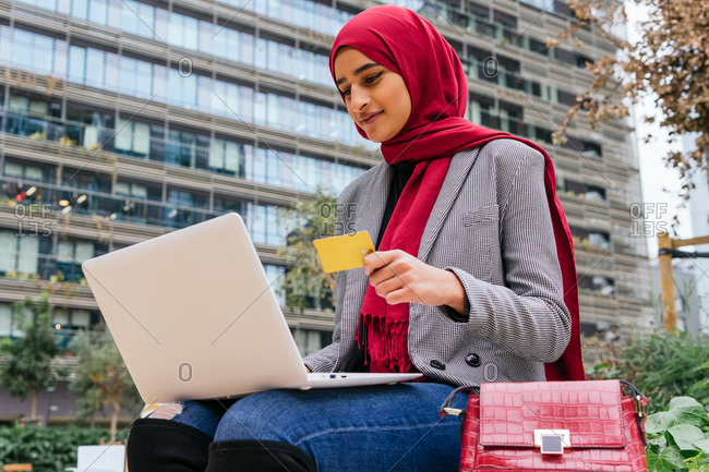 Low angle of Arab female in traditional headscarf sitting on street with laptop and making payment with plastic card during online shopping