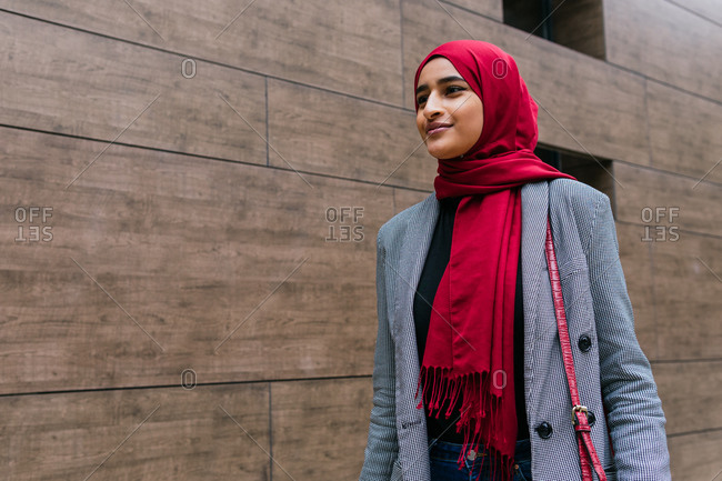 Content young Arab female wearing traditional hijab and casual clothes walking along city street and looking forward