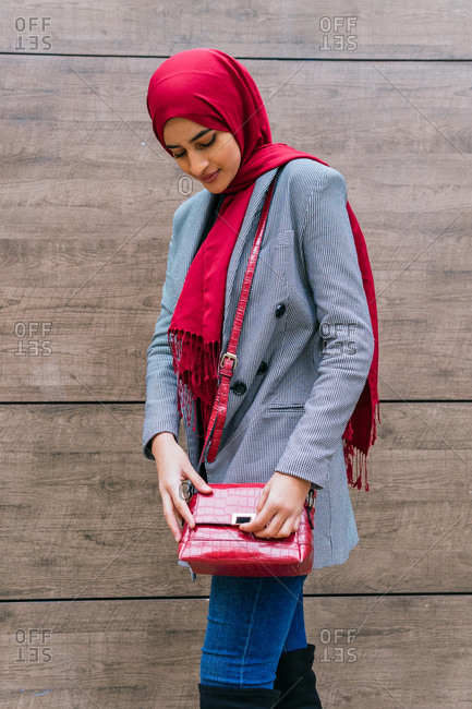 Side view of young content Arab female in hijab and trendy clothes standing near building in city and looking down