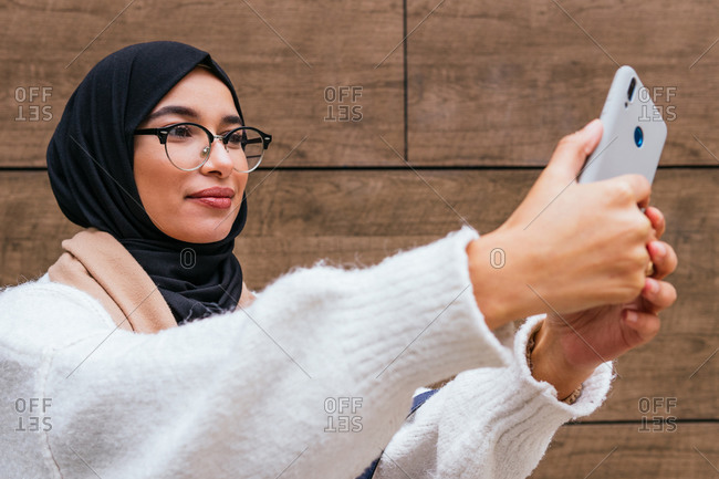 Young Arab female wearing headscarf standing on street and taking photo on selfie camera of smartphone