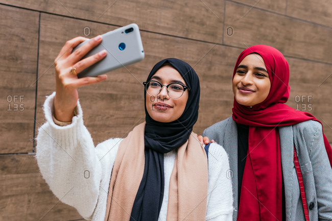 Low angle of Arab female best friends in hijab standing in street and taking selfie on smartphone