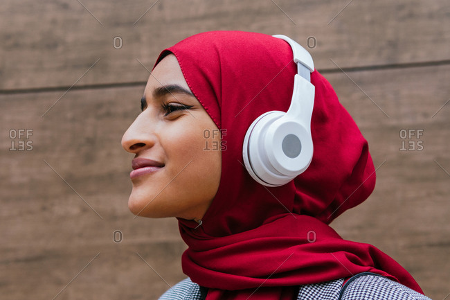 Side view of dreamy Arab female in wireless headphones and traditional hijab standing near urban building and enjoying music looking away