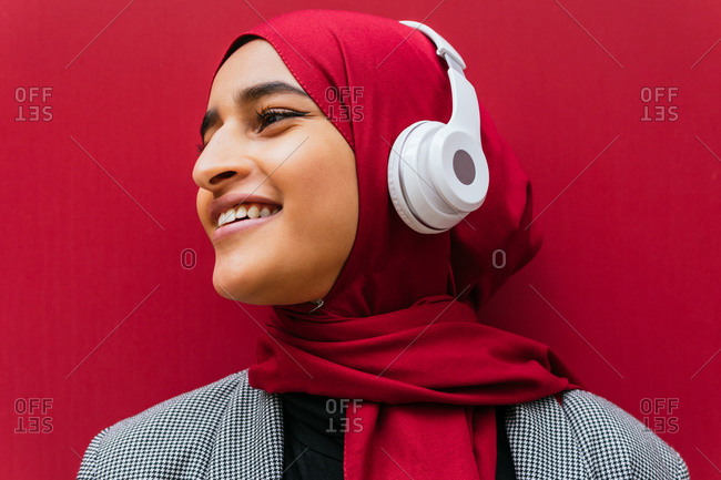 Side view of dreamy Arab female in wireless headphones and traditional hijab standing near urban red building and enjoying music looking away