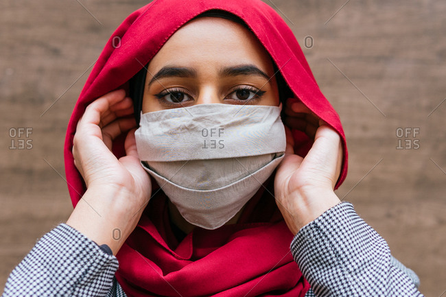 Calm Arab female in hijab standing in street and putting on protective mask during coronavirus epidemic while looking at camera