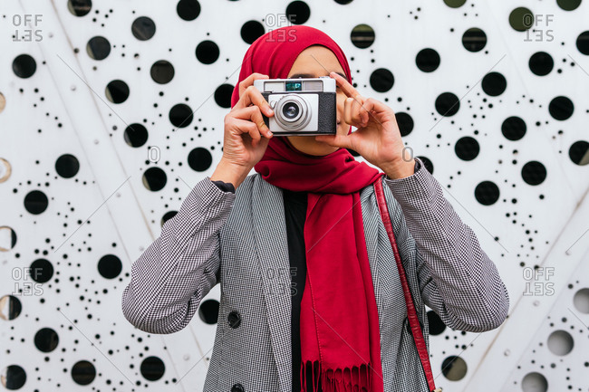 Arab female in red headscarf standing in city with retro photo camera and taking picture