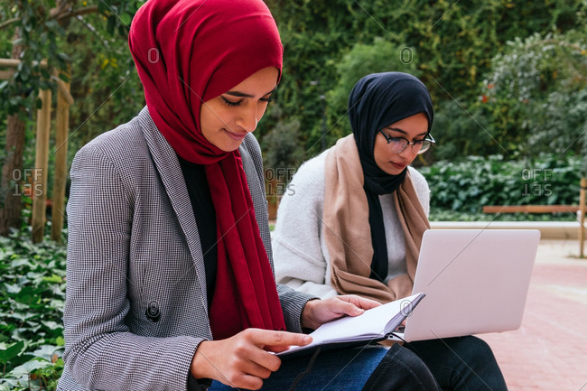 Content Arab female students in headscarf sitting on bench in green garden of campus and preparing for exams while reading notes and using laptop