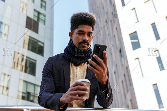 From below focused African American male entrepreneur standing in street with coffee to go and browsing smartphone while reading working emails