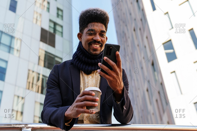 From below cheerful African American male entrepreneur standing in street with coffee to go and browsing smartphone while reading working emails