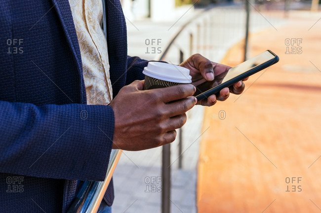 Cropped unrecognizable African American male entrepreneur standing in street with coffee to go and browsing smartphone while reading working emails