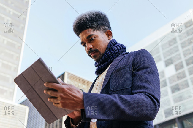 From below of busy African American male freelancer standing in the street browsing on tablet while working remotely on project